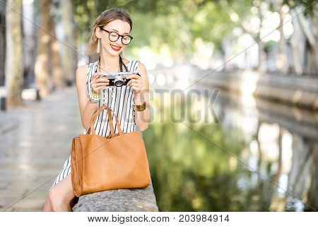 Young woman tourist sitting with photo camera in the park of Nimes city in France