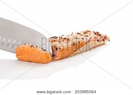 Chef using knife and slicing raw salmon to make fish fillets.