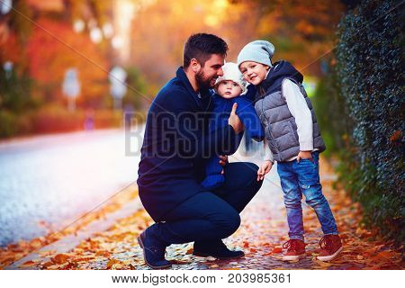Portrait Of Happy Father With Sons On The Walk Along The Autumn Street