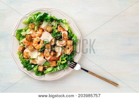 Shrimp Caesar salad with Parmesan cheese, croutons and lettuce, with a fork, shot from above on a light background texture with a place for text
