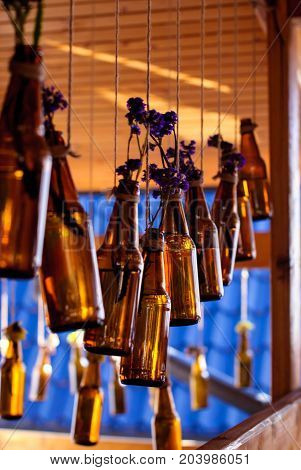 Brown glass bottles with dry blue flowers hanging in the interior for the background.