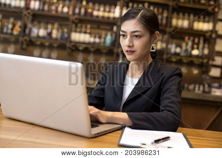 Asian Woman Using Laptop In Restaurant For Work, Woman Working Concept