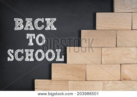 Back to school written on blackboard with wooden blocks