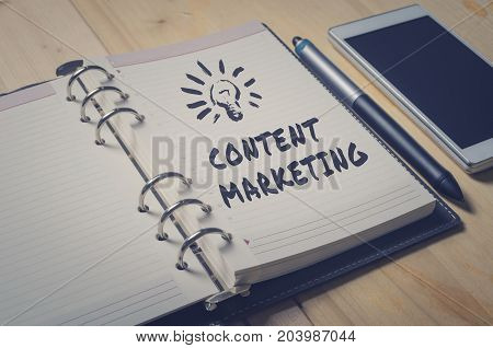 Handwriting of Content Marketing word in notebook for website content concept