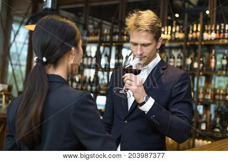 Man Sommelier Tasting Red Wine With Relax Emotion. The Man Is Holding  Wineglass And Smell. Man With