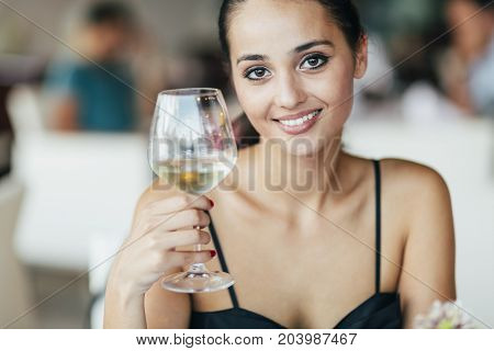 Woman tasting white wine in restaurant and lifting glass accordingly