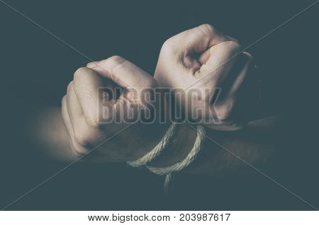 Man with tied hands in low key
