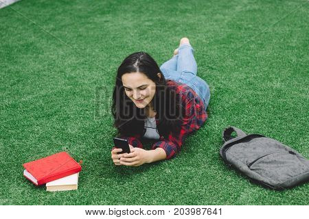 Young Girl Student Laying On The Grass With A Phone In Her Hand.