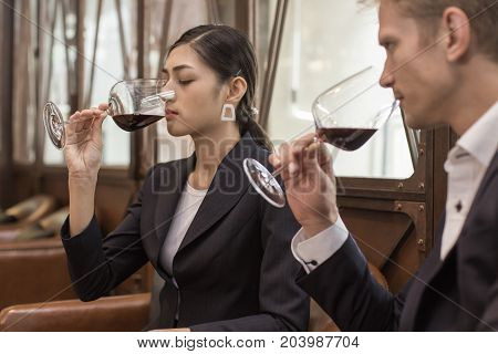 Woman And Man Testing Wine Together At Restaurant. People Drinking Wine With Relax Emotion.