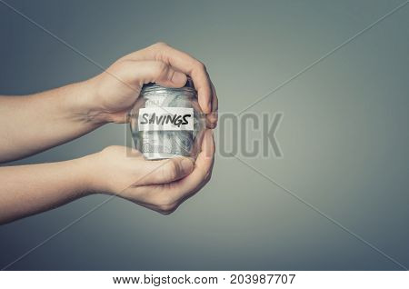 Man hands with glass jar full of US dollars. Saving money concept.