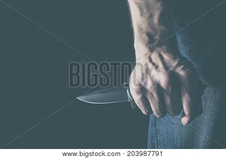 The man with a knife in a hand. Concept of crime and violence.