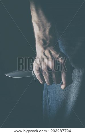 The man with a knife in a hand. Concept of crime violence and terrorism.
