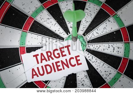 Target audience note on notepaper with dart arrow and dart board. Marketing advertisement business concept.