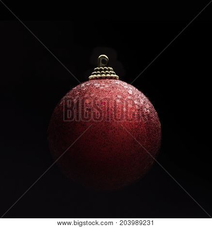 Red color sparkling christmas ball isolated against black background. Gradient light ambiance