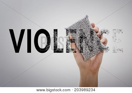 Hand erasing the word VIOLENCE. Stop violence concept.