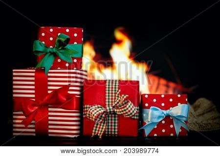 Few giftboxes wrapped in ornamental paper and ribbons arranged on black background with fire.