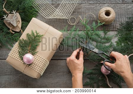 Preparation for Christmas holiday. Christmas Still life of giftbox decor twine fir tree twigs. Woman prepare a gift. Top view and copyspace. Flat lay.
