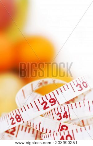 Weight watcher - Measuring tape with different fruits at the background