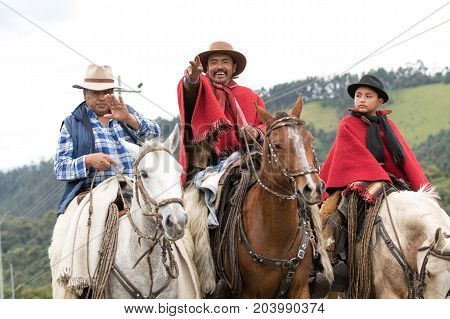 May 27 2017 Sangolqui Ecuador: cowboy raising his hand in greeting while riding a horse towards a rural rodeo in the Andes