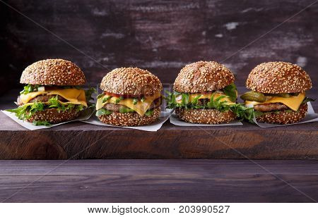 Four homemade hamburgers on wooden table. Buns with sesame seeds beef burgers and various ingredients. Rustic style. Copy space.
