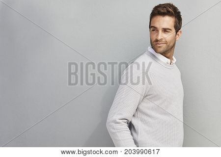 Handsome dude in grey sweater looking over shoulder studio