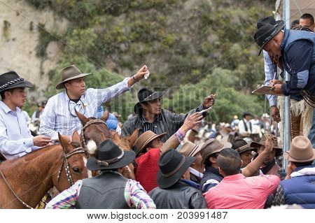 May 27 2017 Sangolqui Ecuador: cowboys paying the entry fee at a rural rodeo in the Andes area