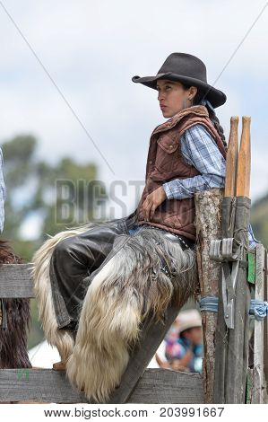 May 27 2017 Sangolqui Ecuador: young female cowboy wering chaps sitting on wooden fence during a rural rodeo