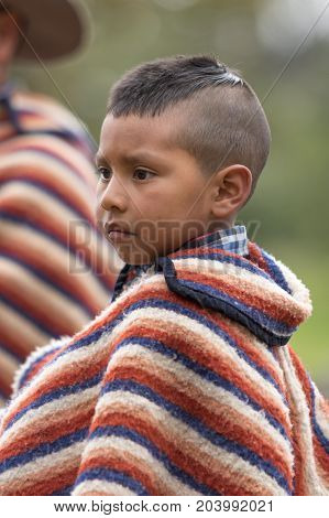 May 27 2017 Sangolqui Ecuador: young indigenous boy wearing traditional wool poncho closeup at a rural rodeo
