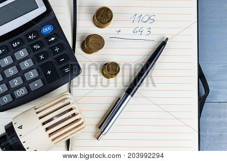 Home heat savings or expenses concept. Radiator regulator with coins and calculator on a notepad.
