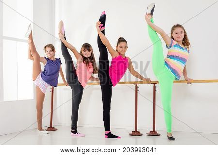 Four smiling young girls using barre while practicing in dance studio. Looking at camera.