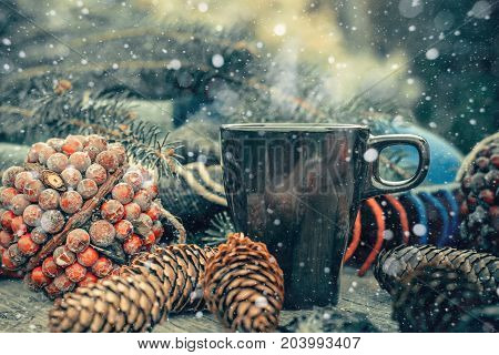 Сup of hot tea on a rustic wooden table. Still life of cones twine patskthread fir branches. Preparing for Christmas. Effect Drawn Snow