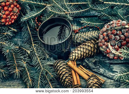 Mug of hot tea on a rustic wooden table. Still life of cones cinnamon fir branches. Preparing for Christmas. Top view.