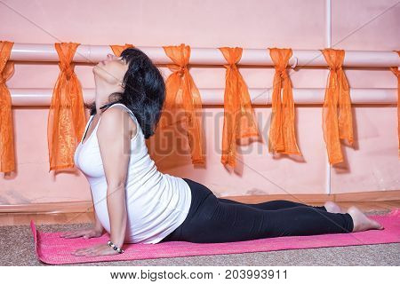 Pregnancy Yoga and Fitness concept. Healthy maternity lifestyle concept. 40 week pregnant middle aged caucasian woman doing yoga exercises laying in cobra pose.