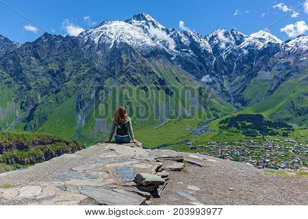 girl sits on cliff's edge and looks at the tops of mountains near the village of Gergeti in Georgia, under Mount Kazbegi. Girl looks at the tops of mountains