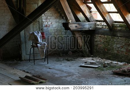Mysterious chair and stained clothes from an abandoned attic