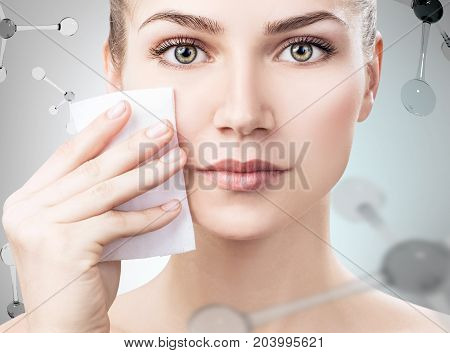 Beautiful young woman remove makeup among molecules over gray background. Innovation cosmetics concept.