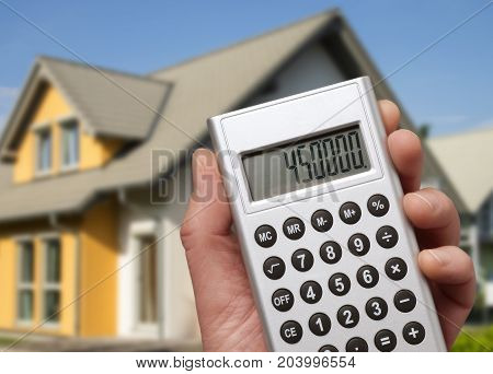 Calculator with a high sum in front of a modern family house
