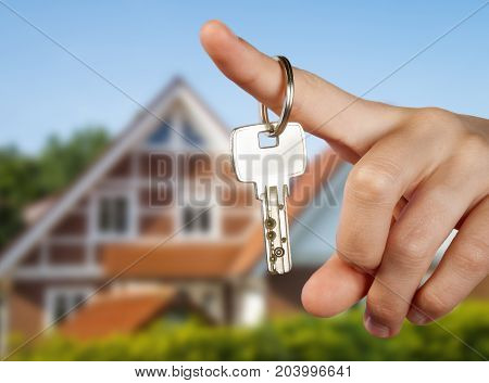Hand holding a key in front of a country house