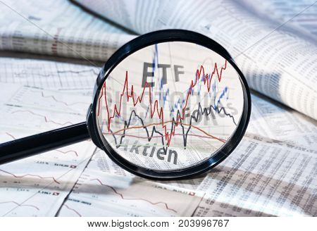 Magnifying glass shows the courses of ETF funds and shares
