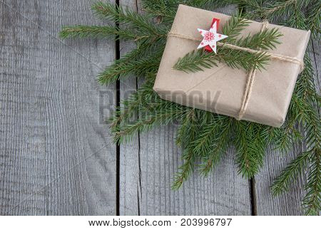 Christmas gift box on wooden table handicraft wrapping parchment twine fir tree twigs cute simple last minute present handmade. Top view.