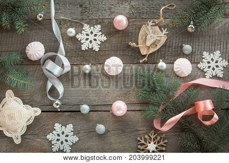 Christmas decor laid out on a wooden surface. Fir branches pink/silver ribbon and ball white marshmallow snowflakes toy deer and decor around. Top view and copyspace. Flat lay. Shabby-chic