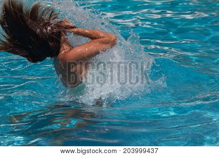 woman splashing water in a pool with her own hair
