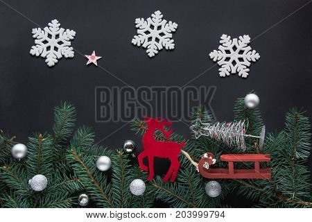 Christmas or New Year decoration concept. A toy of red deer drive by sledge  a Christmas tree on black background with copy space. Top view.