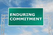 "3D illustration of ""ENDURING COMMITMENT"" script on road sign poster"