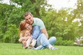 Shot of a happy young loving family having fun outdoors sitting on the grass at the park on a warm summer day hugging and cuddling copyspace parents love couples children kids daughter father mother. poster