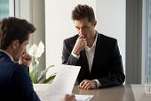 Nervous male job candidate looking with worriment on human resources generalist reading his resume during interview in company office. Millennial man trying to find job, giving application for vacancy poster