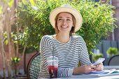 Outdoor photo of pretty European girl dressed casually and trendy as she spends leisure time in cafe outdoors while looking happily at interlocutor listening with interest and holding mobile phone poster