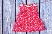 Baby red dress hanging on clothesline. Toddler girl patterned top drying on rope on vintage wooden background. Wet kids apparel in laundry. poster
