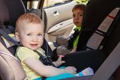 Portrait of two cute white Caucasian toddlers childen sitting in car seats looking in camera. Smiling babies in automobile vehicle fastened with seatbelts. poster