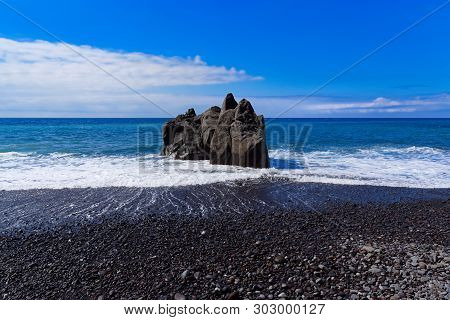 Panoramic View At The Rock Formation On A Beach Against Blue Sky. Praia Formosa Beach In Funchal On